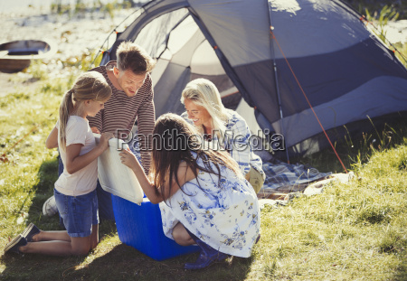family opening cooler outside sunny campsite