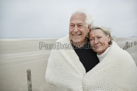 smiling affectionate senior couple wrapped in