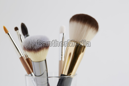 various make up brushes in glass