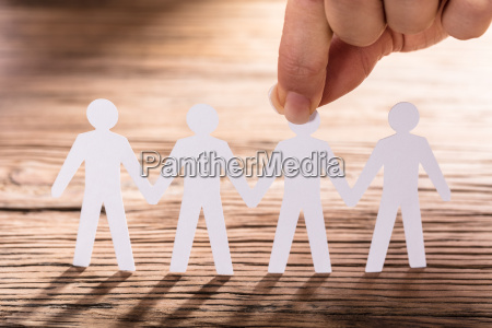 person holding paper cut out figure