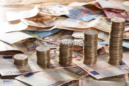 coin stacked on euro notes