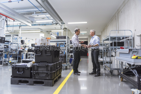 two businessmen shaking hands in factory