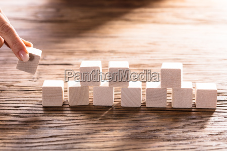 person hand arranging blocks