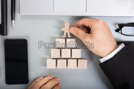 businessperson arranging human figure cut out