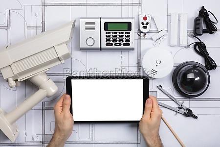 person holding digital tablet on blueprint