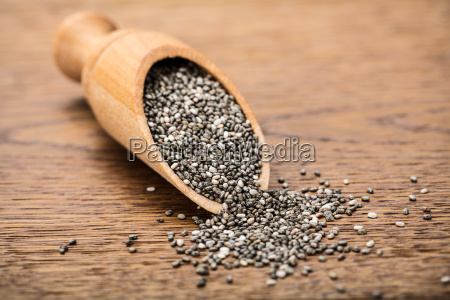 raw chia seeds on wooden scoop
