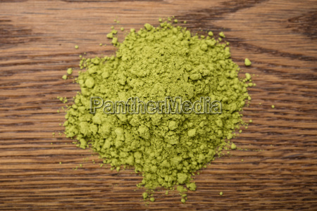 green tea powder on wooden table