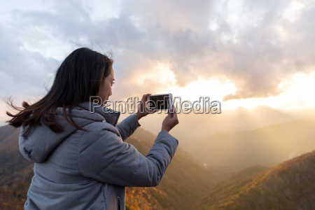 woman taking photo on cellphone at