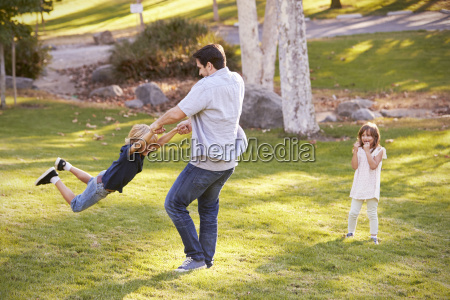 father swinging son by his arms