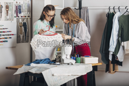 trainee examining dresss fabric by designer
