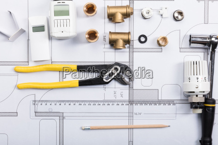 thermostat with work tools on blueprints