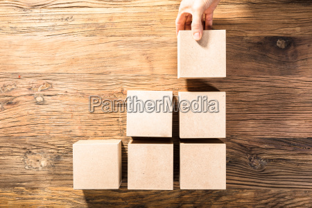 persons hand arranging wooden block