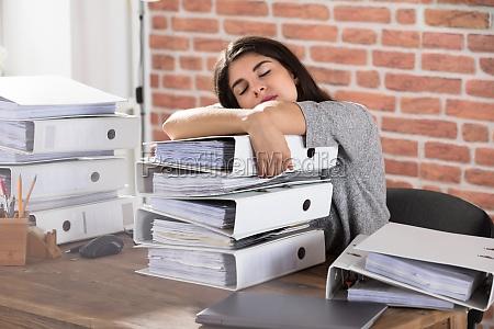 businesswoman sleeping on folder stacked in