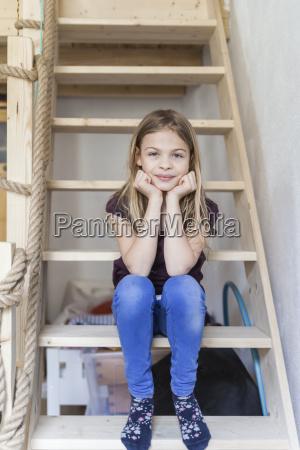 portrait of girl sitting on ladder